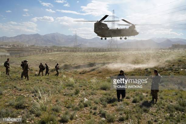 In this photo taken on June 6 a US military Chinook helicopter lands on a field outside the governor's palace during a visit by the commander of US...