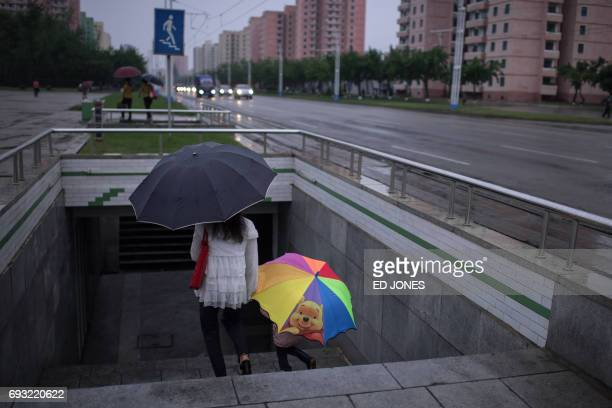 In this photo taken on June 6 a woman and child holding an umbrella with a Winnie the Pooh design enter an underpass in Pyongyang / AFP PHOTO / Ed...