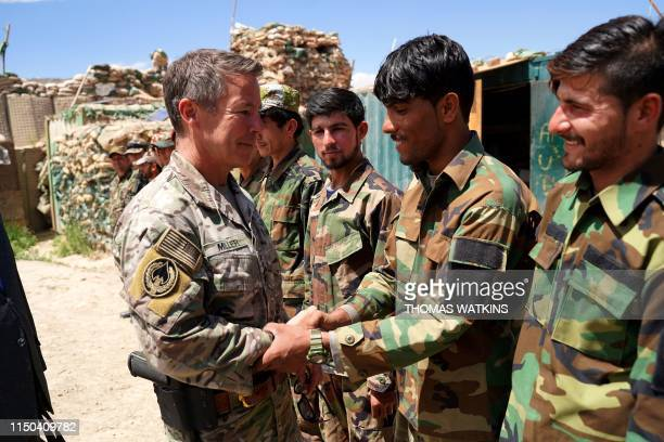 In this photo taken on June 6 commander of US and NATO forces in Afghanistan General Scott Miller shakes hands with Afghan National Army soldiers...