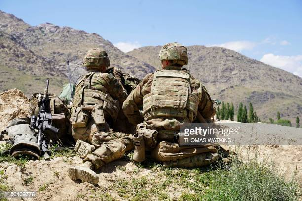 In this photo taken on June 6 US soldiers look out over hillsides during a visit of the commander of US and NATO forces in Afghanistan General Scott...
