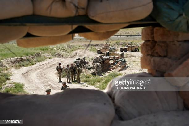 In this photo taken on June 6 US troops are seen through a firing position at the Afghan National Army checkpoint in Nerkh district of Wardak...