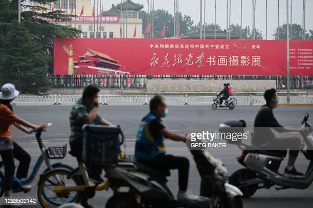 """In this photo taken on June 9 people ride past a propaganda slogan which reads """"Forever Follow the Party"""", outside an exhibition of calligraphy,..."""