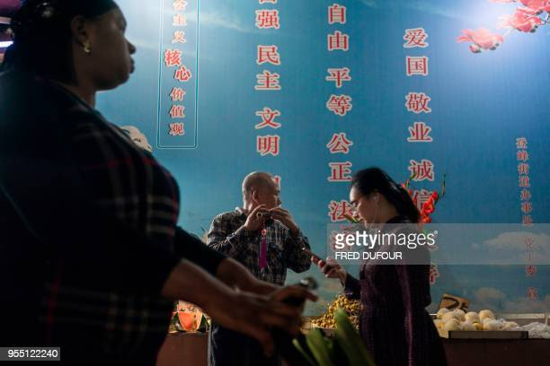 In this photo taken on March 1 a Chinese man plays music as people walk past in the 'Little Africa' district in Guangzhou the capital of southern...