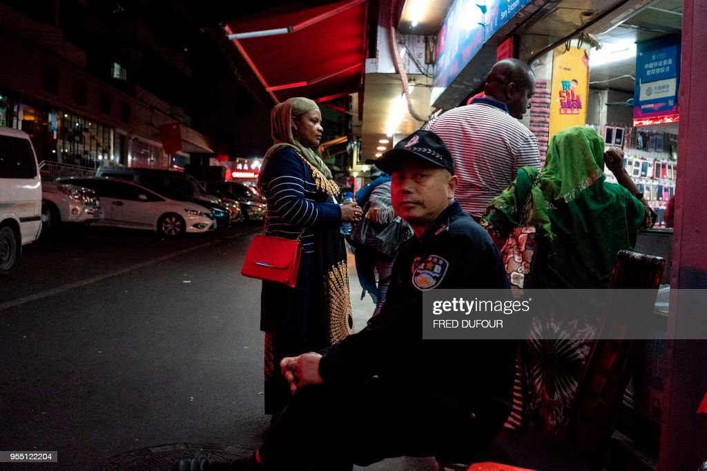 In this photo taken on March 1, 2018, a Chinese security man looks on at the entrance to the 'Little Africa' district in Guangzhou, the capital of southern China's Guangdong province. - The commercial hub has long been a magnet for fortune-seeking Africans, but traders and students say they face unfavourable visa rules and increasingly heavy policing. (Photo by FRED DUFOUR / AFP) / TO