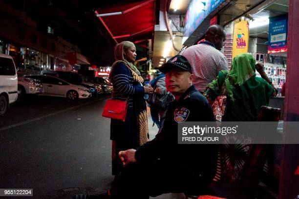 """In this photo taken on March 1 a Chinese security man looks on at the entrance to the """"Little Africa"""" district in Guangzhou, the capital of southern..."""