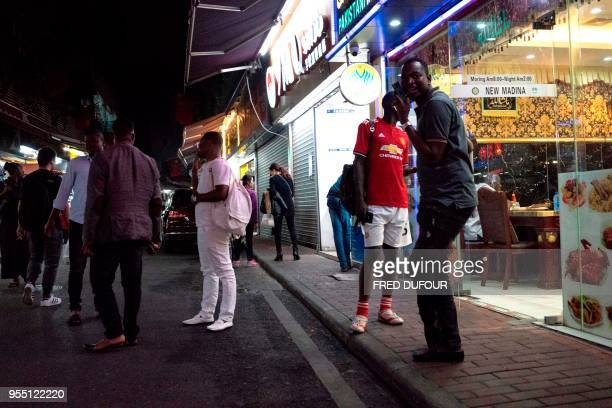 """In this photo taken on March 1 people gather on a street in the """"Little Africa"""" district in Guangzhou, the capital of southern China's Guangdong..."""