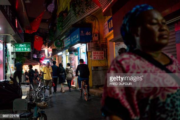 """In this photo taken on March 1 people walk in the """"Little Africa"""" district in Guangzhou, the capital of southern China's Guangdong province. - The..."""