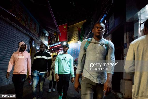 In this photo taken on March 1 people walk in the Little Africa district in Guangzhou the capital of southern China's Guangdong province The...