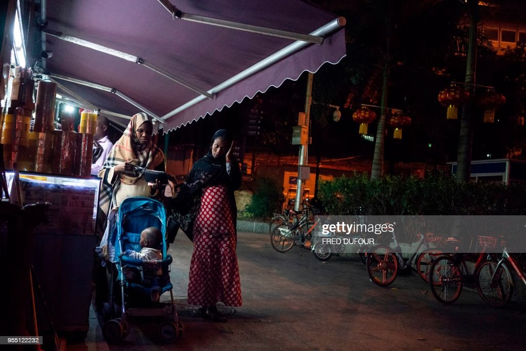 In this photo taken on March 1, 2018, people walk in the 'Little Africa' district in Guangzhou, the capital of southern China's Guangdong province. - The commercial hub has long been a magnet for fortune-seeking Africans, but traders and students say they face unfavourable visa rules and increasingly heavy policing. (Photo by FRED DUFOUR / AFP) / TO
