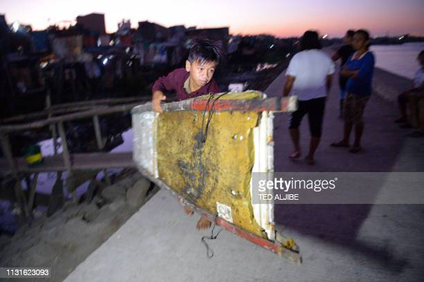 In this photo taken on March 10 13yearold Reymark Cavesirano carries his borrowed makeshift craft made from styrofoam to the water as he prepares to...