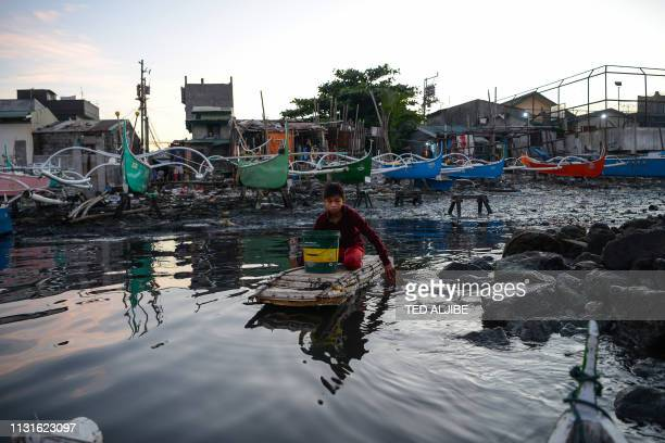 In this photo taken on March 10 13yearold Reymark Cavesirano paddles his borrowed makeshift craft made from styrofoam to fishing boats anchored at...