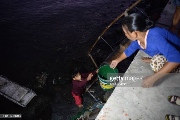 In this photo taken on March 10 13yearold Reymark Cavesirano takes a bucket from his mother as he prepares to paddle his borrowed makeshift craft...