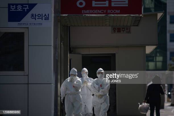In this photo taken on March 12 medical workers wearing protective clothing against the COVID-19 novel coronavirus walks between buildings at the...