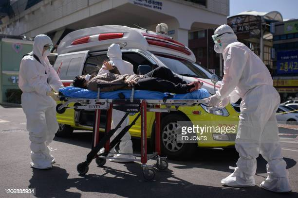 In this photo taken on March 12 medical workers wearing protective clothing against the COVID-19 novel coronavirus attend to a woman with unknown...