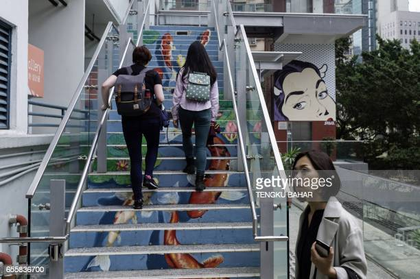 In this photo taken on March 12 visitors walk up stairs adorned with artwork depicting fish in a pond as a pop art installation is seen in the...