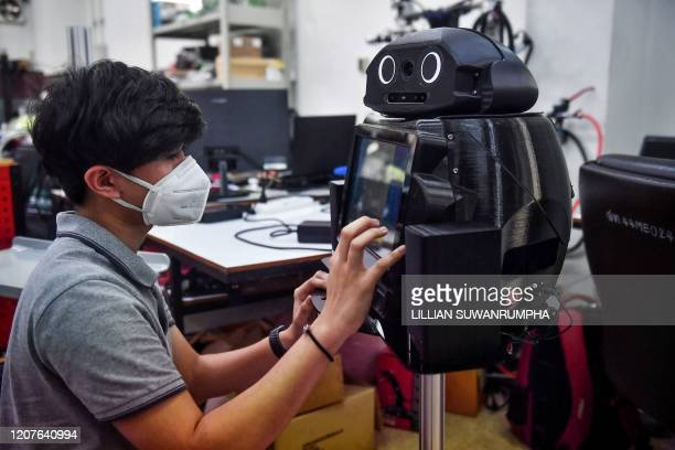 In this photo taken on March 18, 2020 an engineering student configures a medical robot modified to screen and observe COVID-19 coronavirus patients...