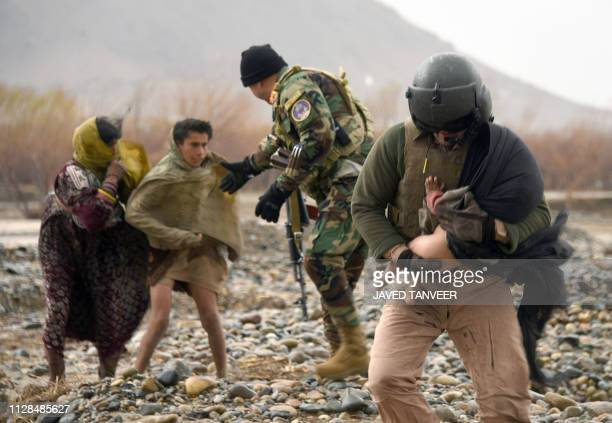 TOPSHOT In this photo taken on March 2 An Afghan air force crew member carries a child during an evacuation operation in a flood affected area of...