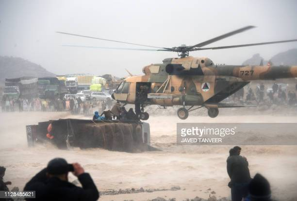 TOPSHOT In this photo taken on March 2 an Afghan military helicopter rescues people from atop an overturned truck in flooded area of Arghandab...