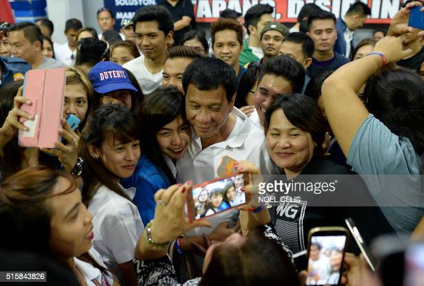 In this photo taken on March 2 shows Davao City Mayor and Presidential Candidate Rodrigo Duterte huddling with college students during his campaign...