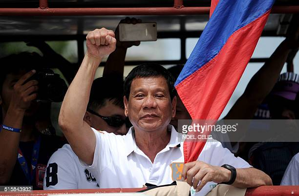 In this photo taken on March 2 shows Davao City Mayor and Presidential Candidate Rodrigo Duterte raising a clenched fist during his campaign sortie...