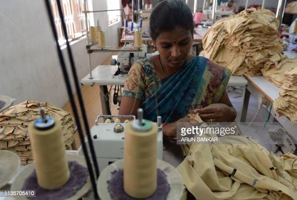 In this photo taken on March 25 Indian labourer Jothi stitches apparel at the tailoring section of a production unit in the south Indian city of...