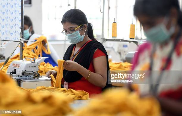 In this photo taken on March 25 Indian labourers stitch apparel in the tailoring section of a textile production unit in the south Indian city of...