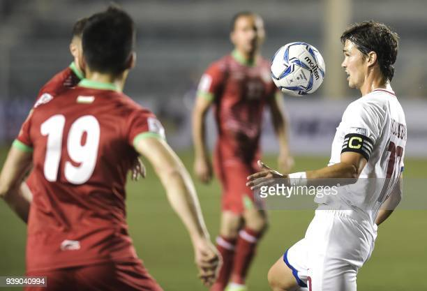 In this photo taken on March 27 2018 shows Phil Younghusband of the Philippines controlling the ball against Tajikistan during their football AFC...