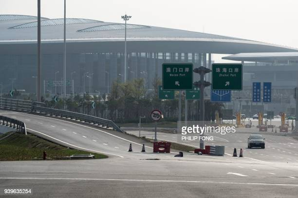 In this photo taken on March 28 a car passes toll booths of Zhuhai Port along a section of the Hong KongZhuhaiMacau Bridge in Zhuhai Officials say...