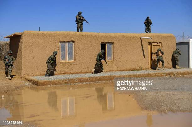 TOPSHOT In this photo taken on March 3 Afghan National Army soldiers take part in a drill exercise at a military base in the Guzara district of Herat...