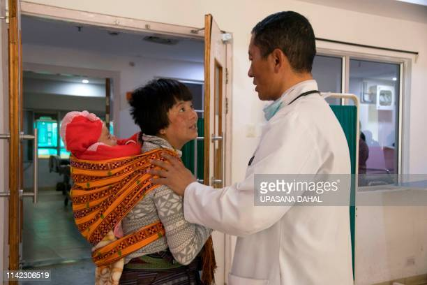 In this photo taken on March 30 Bhutan's Prime Minister Lotay Tshering speaks with a patient as he does rounds at the National Referral Hospital in...