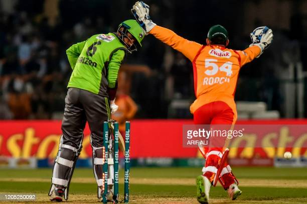 In this photo taken on March 4 Lahore Qalandars's Muhammad Faizan watches after being bowled out by Islamabad United's Zafar Gohar as teammate Luke...