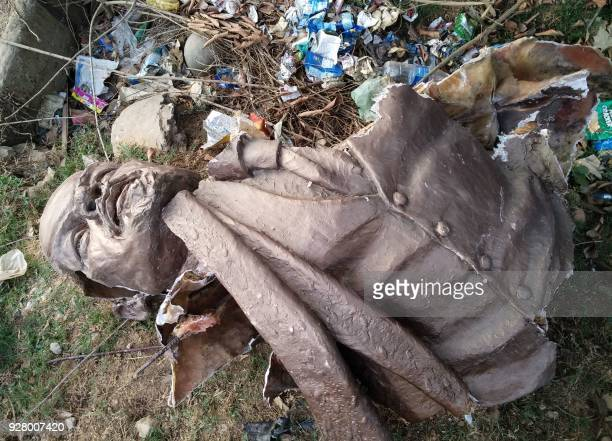 In this photo taken on March 5 2018 the bust of a Lenin statue is seen laying on the ground after Indian supporters of Bharatiya Mazdoor Sangh a wing...