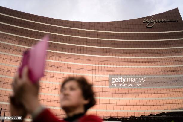 In this photo taken on March 5 a woman takes a selfie outside the Wynn casino resort in Macau The trade war may have sent ripples of uncertainty...
