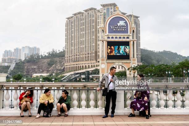 In this photo taken on March 5 visitors stand on a bridge on the grounds of the Venetian casino resort in Macau The trade war may have sent ripples...