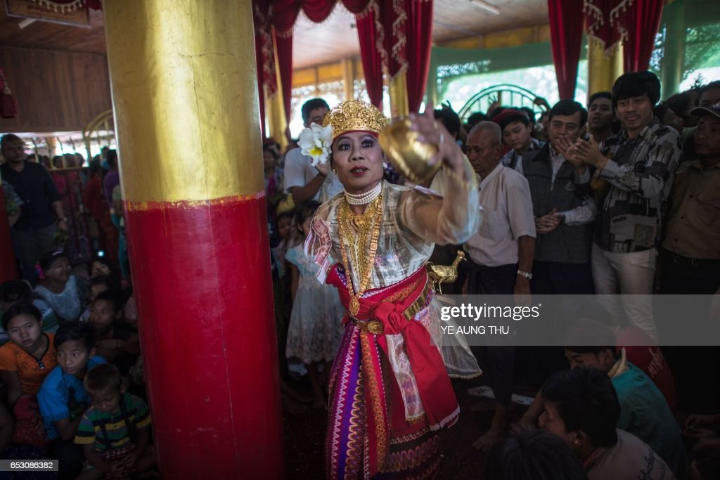In this photo taken on March 7, 2017, a crowd watches a medium dance as he invokes spirits inside a shrine in Shwe Ku Ni village during the Ko Gyi Kyaw Nat festival. The medium spins around in a frenzy of red and gold while glugging from a bottle of whiskey, part of an age old ritual to honour Myanmar's spirit guardian of drunkards and gamblers. Every year thousands of people pour into a small village southwest of Mandalay for a two-week festival, many packed into boats clutching bags of food and bedding or pulling up on rickety old bullock carts. / AFP PHOTO / Ye Aung THU