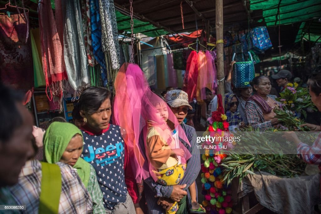 In this photo taken on March 7, 2017, a family walks past food vendors as they arrive in Shwe Ku Ni village for the Ko Gyi Kyaw Nat festival. The medium spins around in a frenzy of red and gold while glugging from a bottle of whiskey, part of an age old ritual to honour Myanmar's spirit guardian of drunkards and gamblers. Every year thousands of people pour into a small village southwest of Mandalay for the two-week festival, many packed into boats clutching bags of food and bedding or pulling up on rickety old bullock carts. / AFP PHOTO / Ye Aung THU