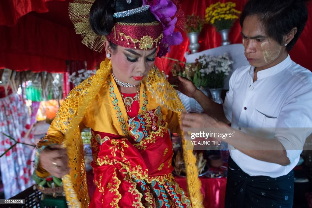 In this photo taken on March 7, 2017, a medium gets dressed inside a shrine in Shwe Ku Ni village as he prepares to participate in the Ko Gyi Kyaw Nat festival. The medium spins around in a frenzy of red and gold while glugging from a bottle of whiskey, part of an age old ritual to honour Myanmar's spirit guardian of drunkards and gamblers. Every year thousands of people pour into a small village southwest of Mandalay for a two-week festival, many packed into boats clutching bags of food and bedding or pulling up on rickety old bullock carts. / AFP PHOTO / Ye Aung THU