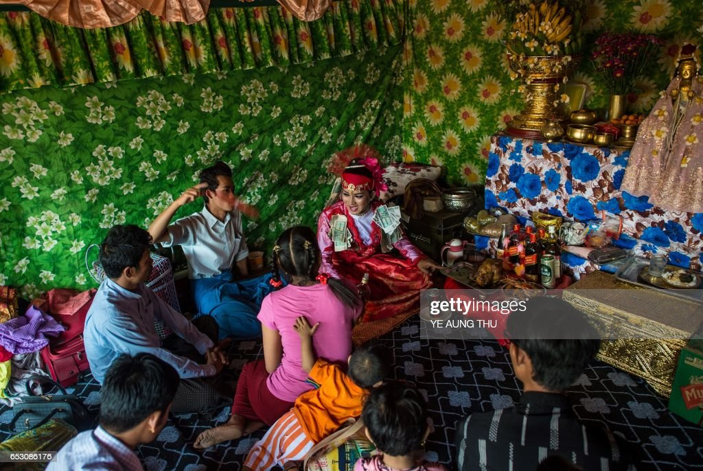 In this photo taken on March 7, 2017, a medium sits among devotees inside a shrine in Shwe Ku Ni village during the Ko Gyi Kyaw Nat festival. The medium spins around in a frenzy of red and gold while glugging from a bottle of whiskey, part of an age old ritual to honour Myanmar's spirit guardian of drunkards and gamblers. Every year thousands of people pour into a small village southwest of Mandalay for a two-week festival, many packed into boats clutching bags of food and bedding or pulling up on rickety old bullock carts. / AFP PHOTO / Ye Aung THU