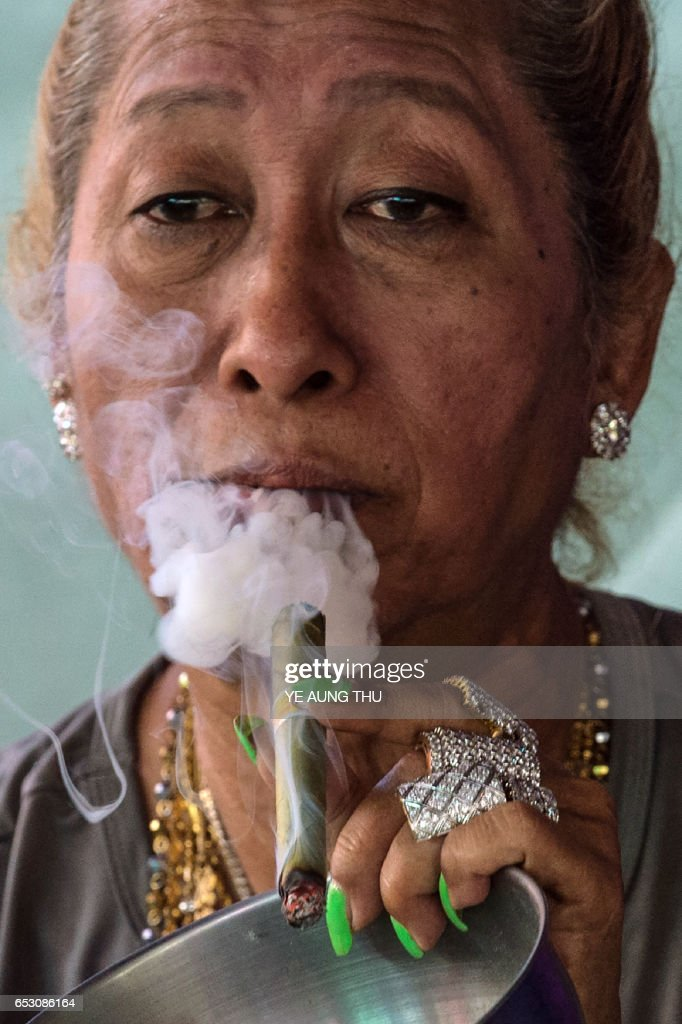 In this photo taken on March 7, 2017, a medium smokes a cigar inside a shrine in Shwe Ku Ni village as she participates in the Ko Gyi Kyaw Nat festival. The medium spins around in a frenzy of red and gold while glugging from a bottle of whiskey, part of an age old ritual to honour Myanmar's spirit guardian of drunkards and gamblers. Every year thousands of people pour into a small village southwest of Mandalay for a two-week festival, many packed into boats clutching bags of food and bedding or pulling up on rickety old bullock carts. / AFP PHOTO / Ye Aung THU