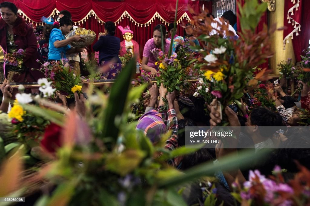 In this photo taken on March 7, 2017, devotees clutch flower arrangements and other offerings inside shrine in Shwe Ku Ni village as they participate in the Ko Gyi Kyaw Nat festival. The medium spins around in a frenzy of red and gold while glugging from a bottle of whiskey, part of an age old ritual to honour Myanmar's spirit guardian of drunkards and gamblers. Every year thousands of people pour into a small village southwest of Mandalay for a two-week festival, many packed into boats clutching bags of food and bedding or pulling up on rickety old bullock carts. / AFP PHOTO / Ye Aung THU