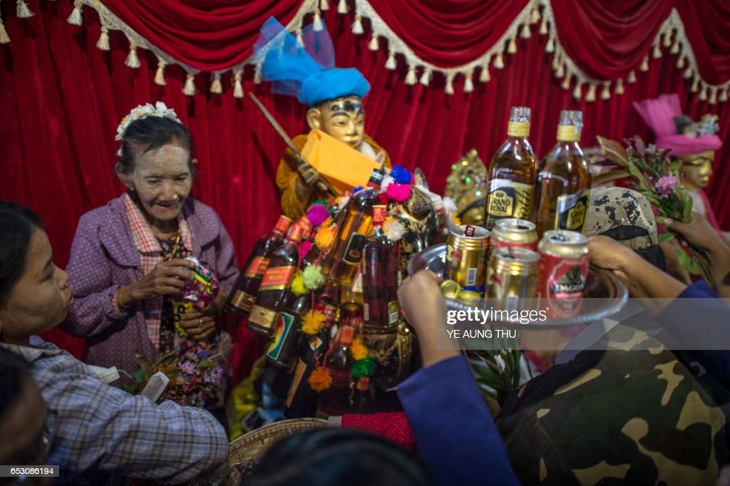 In this photo taken on March 7, 2017, devotees make offerings inside a shrine in Shwe Ku Ni village during the Ko Gyi Kyaw Nat festival. The medium spins around in a frenzy of red and gold while glugging from a bottle of whiskey, part of an age old ritual to honour Myanmar's spirit guardian of drunkards and gamblers. Every year thousands of people pour into a small village southwest of Mandalay for the two-week festival, many packed into boats clutching bags of food and bedding or pulling up on rickety old bullock carts. / AFP PHOTO / Ye Aung THU
