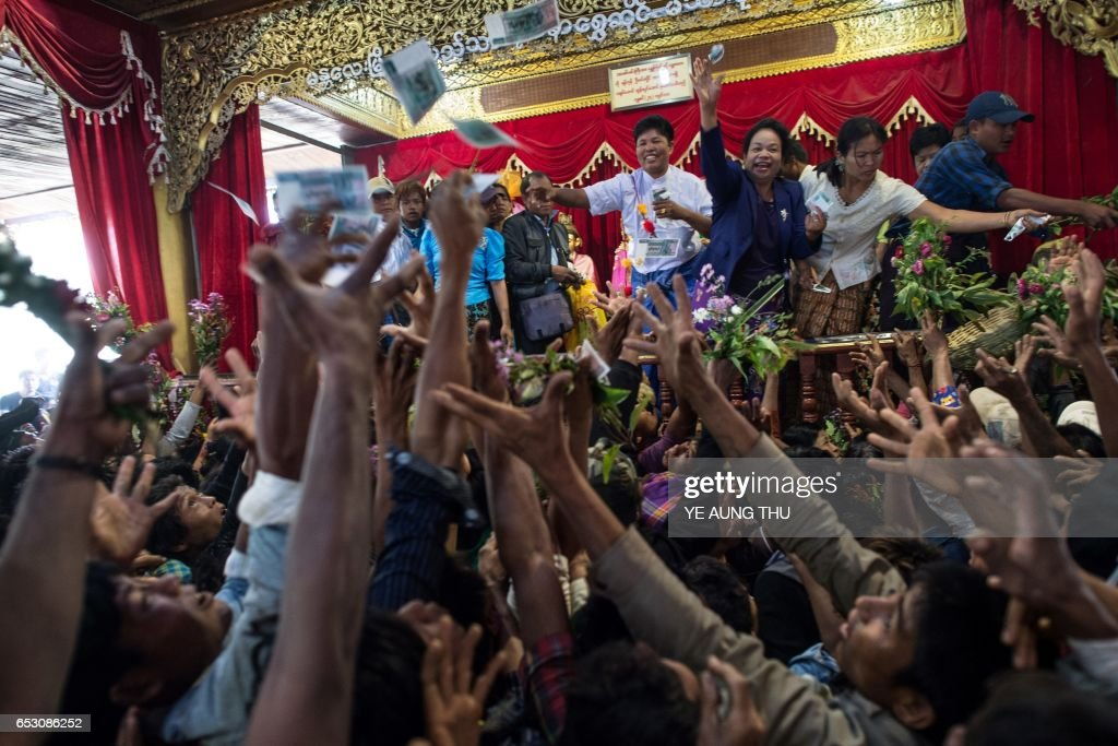 In this photo taken on March 7, 2017, devotees scramble to reach currency notes thrown into the crowd by wealthy participants inside a shrine in Shwe Ku Ni village during the Ko Gyi Kyaw Nat festival. The medium spins around in a frenzy of red and gold while glugging from a bottle of whiskey, part of an age old ritual to honour Myanmar's spirit guardian of drunkards and gamblers. Every year thousands of people pour into a small village southwest of Mandalay for a two-week festival, many packed into boats clutching bags of food and bedding or pulling up on rickety old bullock carts. / AFP PHOTO / Ye Aung THU