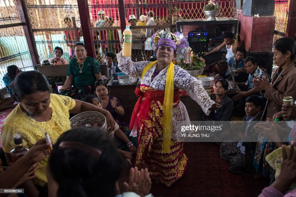 In this photo taken on March 7, 2017, devotees watch a medium invoke spirits inside a shrine in Shwe Ku Ni village during the Ko Gyi Kyaw Nat festival. The medium spins around in a frenzy of red and gold while glugging from a bottle of whiskey, part of an age old ritual to honour Myanmar's spirit guardian of drunkards and gamblers. Every year thousands of people pour into a small village southwest of Mandalay for the two-week festival, many packed into boats clutching bags of food and bedding or pulling up on rickety old bullock carts. / AFP PHOTO / Ye Aung THU