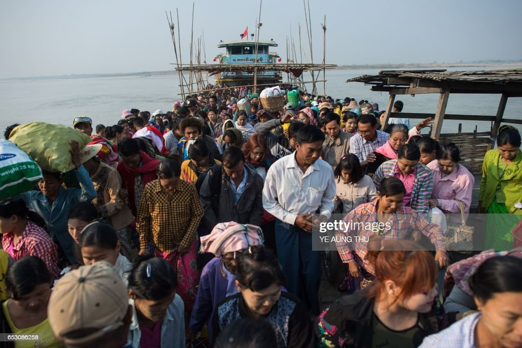 In this photo taken on March 7, 2017, people disembark from a ferry on the banks of the Chindwin river in central Myanmar near Pakhangyi town as they head to participate in the Ko Gyi Kyaw Nat festival. The medium spins around in a frenzy of red and gold while glugging from a bottle of whiskey, part of an age old ritual to honour Myanmar's spirit guardian of drunkards and gamblers. Every year thousands of people pour into a small village southwest of Mandalay for a two-week festival, many packed into boats clutching bags of food and bedding or pulling up on rickety old bullock carts. / AFP PHOTO / Ye Aung THU