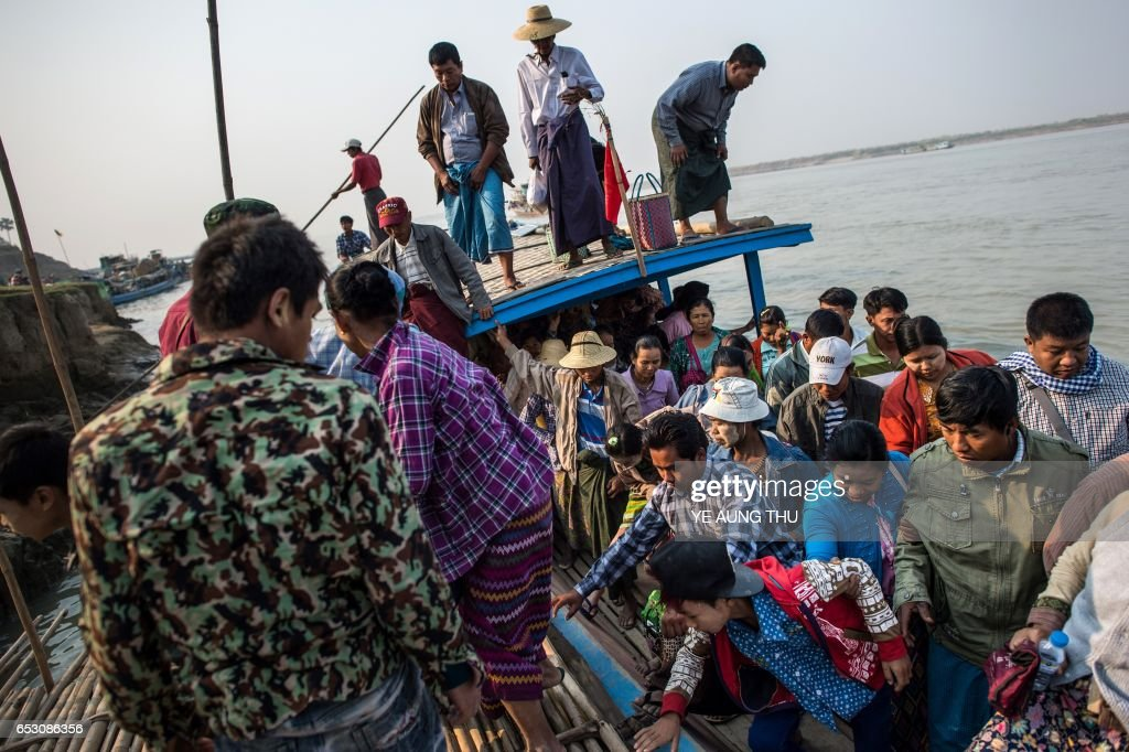 In this photo taken on March 7, 2017, people disembark from a ferry on the banks of the Chindwin river in central Myanmar near Pakhangyi town as they head to participate in the Ko Gyi Kyaw Nat festival. The medium spins around in a frenzy of red and gold while glugging from a bottle of whiskey, part of an age old ritual to honour Myanmar's spirit guardian of drunkards and gamblers. Every year thousands of people pour into a small village southwest of Mandalay for the two-week festival, many packed into boats clutching bags of food and bedding or pulling up on rickety old bullock carts. / AFP PHOTO / Ye Aung THU