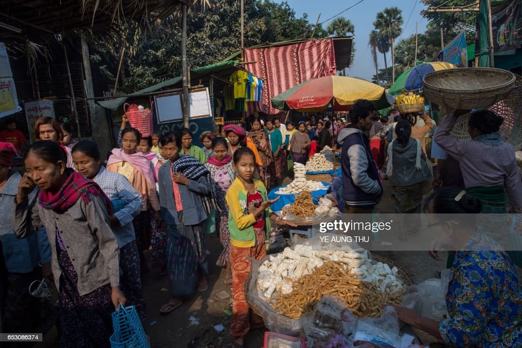 In this photo taken on March 7, 2017, people walk past food vendors as they arrive in Shwe Ku Ni village for the Ko Gyi Kyaw Nat festival. The medium spins around in a frenzy of red and gold while glugging from a bottle of whiskey, part of an age old ritual to honour Myanmar's spirit guardian of drunkards and gamblers. Every year thousands of people pour into a small village southwest of Mandalay for a two-week festival, many packed into boats clutching bags of food and bedding or pulling up on rickety old bullock carts. / AFP PHOTO / Ye Aung THU