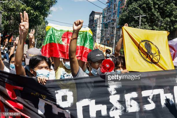 In this photo taken on May 11, 2021 protesters hold banners and placards as they march during a demonstration against the military coup in Yangon.