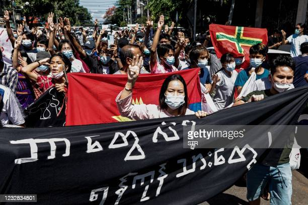 In this photo taken on May 11, 2021 protesters hold up the three finger salute as they march during a demonstration against the military coup in...