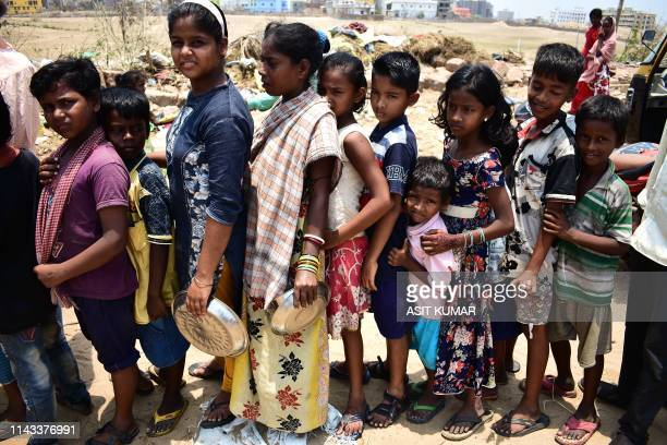 TOPSHOT In this photo taken on May 12 Indian children queue to collect food handouts in Puri in the eastern Indian state of Odisha following Cyclone...