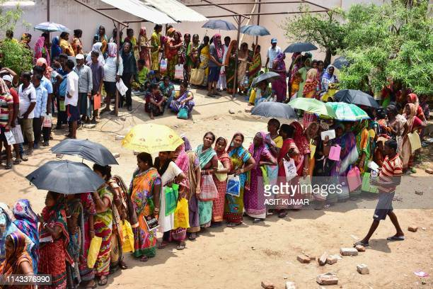 TOPSHOT In this photo taken on May 12 Indian residents queue to collect relief materials in Puri in the eastern Indian state of Odisha following...